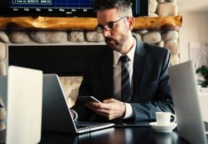 Business Man Texting on Phone at Desk