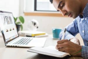 Man Writing Notes at Desk
